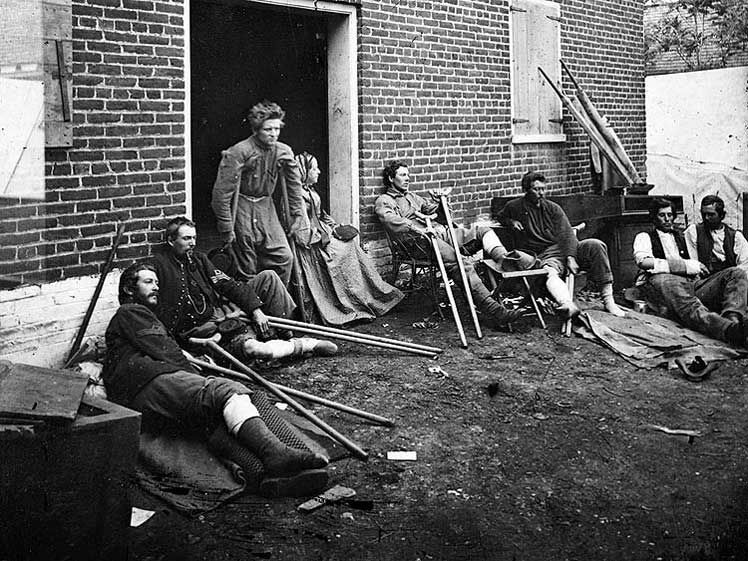 Soldiers resting outside a field hospital